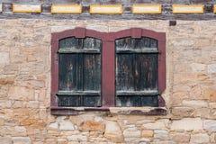 Windows con gli otturatori chiusi in una parete dell'arenaria Immagini Stock Libere da Diritti