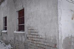 Windows con la reja y el ladrillo del hierro arruinó la pared imagen de archivo libre de regalías