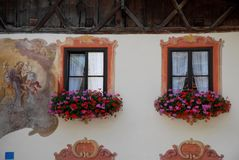 Windows with curtains and flowers in Oberammergau in Germany. Photo made in Oberammergau in Bavaria (Germany). The picture shows a portion of the facade of one Royalty Free Stock Images