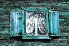 Windows with curtains and shutters at an old green-blue wooden house stock images