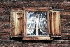 Windows with curtains and shutters on an old wooden house royalty free stock image
