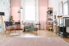 Windows with curtains. Windows with white and pink curtains in bright kid bedroom interior with lamps, pink chairs and soft carpet stock photo