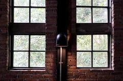 Windows da casa do sótão com a lâmpada na parede de tijolo imagens de stock
