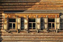 Windows da casa tradicional de madeira do russo construída no estilo country do russo foto de stock royalty free