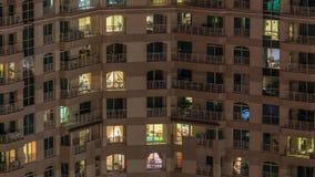 Windows da construção do multi-andar com iluminação para dentro e de povos móveis no timelapse dos apartamentos filme