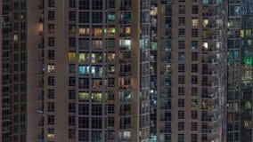 Windows da construção do multi-andar com iluminação para dentro e de povos móveis no timelapse dos apartamentos video estoque