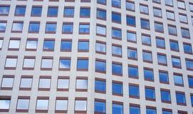 Windows dans l'immeuble de bureaux reflétant le ciel bleu Photos libres de droits