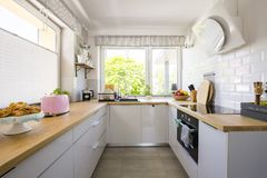 Windows dans l'intérieur blanc de cuisine avec les coffrets gris et en bois photos stock