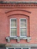 Windows dans un mur de briques rouge Photographie stock libre de droits