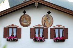Windows with dark green, white curtains and flowers in Oberammergau in Germany. Photo made in Oberammergau in Bavaria (Germany). The picture shows the upper part Royalty Free Stock Photos