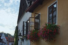 Windows decorated with red flowers in flower boxes during summer sunset. Old town of Cesky Krumlov, Czech Republic Stock Photo