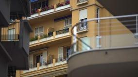 Windows del bloque de viviendas de varios pisos en ciudad europea, balcones con las flores metrajes