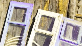 The windows are in different colors in retro style. Stand near the wooden wall. Stock Photos