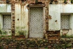 Windows and doors of an abandoned house covered with bricks. Emergency condition stock photo