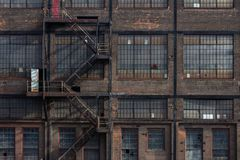 Windows, doors, and fire escape on the exterior of a derelict industrial building. Horizontal aspect stock images