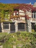 Windows e porte con le barre su una vecchia casa di pietra a vi medievale Fotografie Stock
