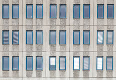 Windows. Elongated narrow windows in three rows of grooved concrete facade Royalty Free Stock Images