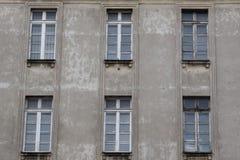Windows en la fachada de la casa gris vieja desigual Imagenes de archivo
