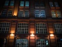 Windows en una pared de ladrillo un negocio-edificio pasado de moda con la iluminación de la noche foto de archivo