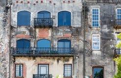 Windows et fer noir sur le vieux mur de briques Images stock
