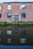 Windows et porte du côté d'un vieux, industriel, rouge immeuble de brique à côté du canal de Birmingham Photo stock