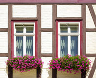Windows with flower boxes at frame-work house Royalty Free Stock Images