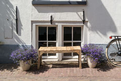 Windows, flowers, bench and bicycle - typical Dutch street scene Stock Photos