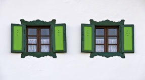 Windows with green fringes and shutters. Two wooden windows with green fringes and shutters at a white wall Royalty Free Stock Photos