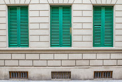 Windows with green shutters. Old house on the streets of Florence with closed shutters, Tuscany, Italy Stock Photo