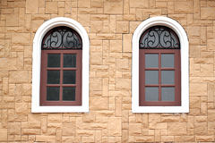 Windows of homes with brick wall surround. Royalty Free Stock Photo