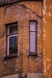 Windows i ett gammalt hus med den brutna färgrika fasaden Royaltyfria Bilder
