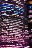 Windows i skyskrapanatten med det kulöra filtret Royaltyfri Bild
