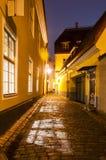 Windows ilumina a queda para baixo na pedra de pavimentação na cidade velha na noite Fotografia de Stock Royalty Free