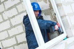 Windows-Installation Bauarbeiter, die Rahmen in Öffnung installieren stockfotografie