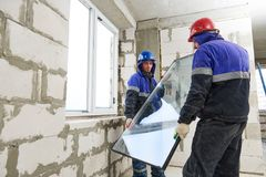 Windows installation. Two construction workers installing glass. Windows installation. Two male industrial building workers installing glass into frame at royalty free stock image