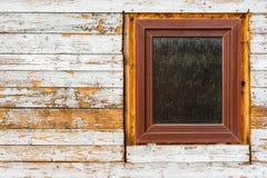 Windows installerade i gammalt trähus och att skala målarfärg på träplankor som bär textur arkivfoton