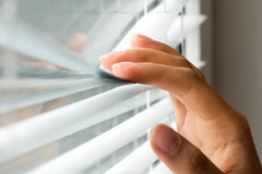 Windows jalousie. woman peeking through window blinds. Male hand separating slats of venetian blinds with a finger to royalty free stock photography