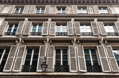 Windows with joalousies in Paris. Rows of windows decorated with jalousies and black forged balconet Royalty Free Stock Image