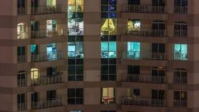 Windows kondygnacja budynek z oświetleniem wśrodku i ruszać się ludzi w mieszkania timelapse zbiory