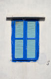 Windows. A lonely window with blue shutters on a white wall royalty free stock photo
