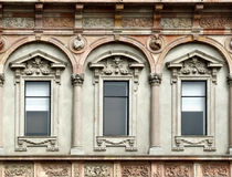 Windows of Milan University. Three windows with ornamental decoration above and under - beautiful ornate wall Stock Image