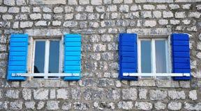 Windows mit den blauen Vorhängen Stockfotos