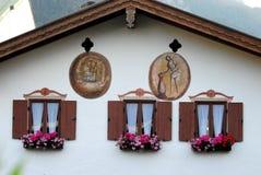 Windows mit den dunkelgrünen, weißen Vorhängen und den Blumen in Oberammergau in Deutschland Lizenzfreie Stockfotos