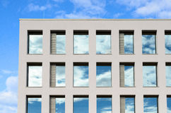 Windows in a modern office block reflect the sky Stock Photos