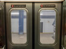 Windows of a moving subway train looking out into station platfo Stock Photo