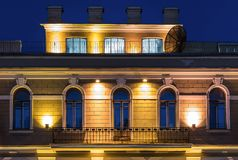 Windows on night facade and mansard of office building. Several windows in a row and balcony on night illuminated facade and mansard of urban office building Royalty Free Stock Photography