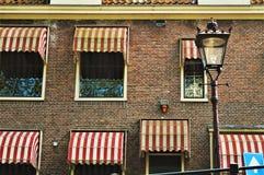 Windows och lampa i Amsterdam, Nederländerna, Europa och färgrika byggnader Arkivfoton