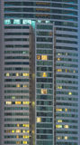 Windows of office buildings illuminated at night Stock Images