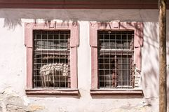 Windows on the old abandoned house used as prison during the war with metal safety gratings bars or grills from the outside.  stock photography