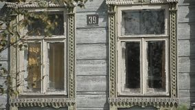 Windows of an old wooden house. The wind sways the tree branches stock video footage